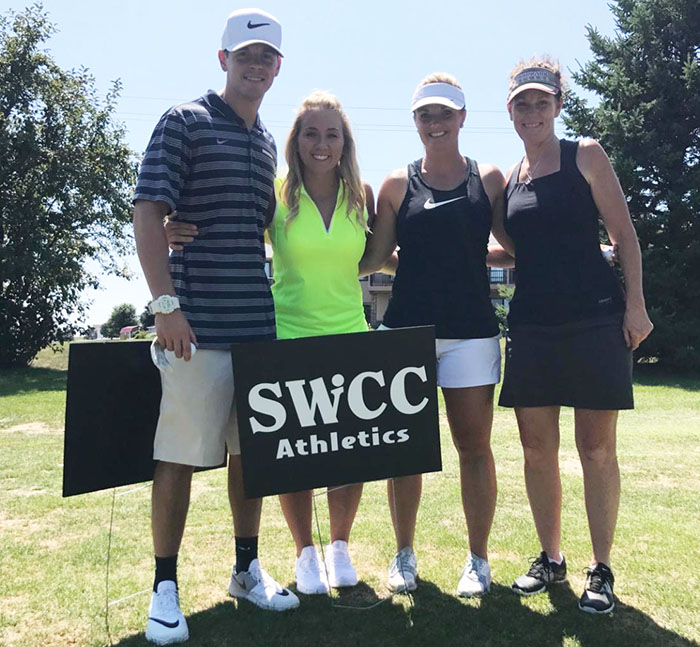 SWCC golf team posing with SWCC sign at tournament