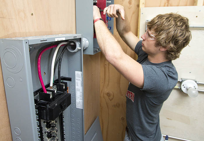 Electrical student working on panel