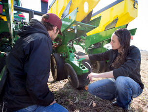 Two students fixing combine