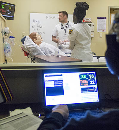 Students examing patient simulator with computer screen in foreground