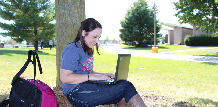 Female student with laptop leaning on tree outside