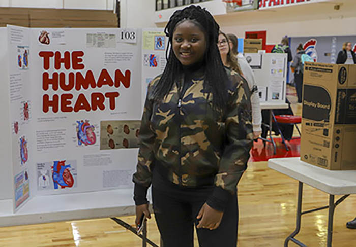 Student in front of her heart disease poster at Fall 2018 Poster Day