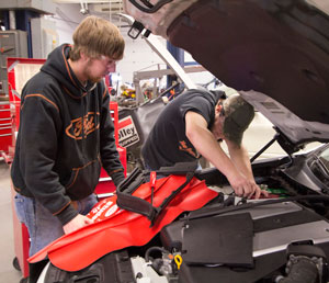 Two students working under hood of car