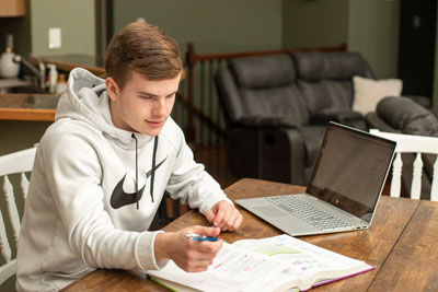 Student at kitchen table working on online class