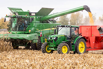 Combine and tractor harvesting in corn field