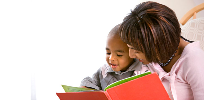 lady in pink sweater reading to child