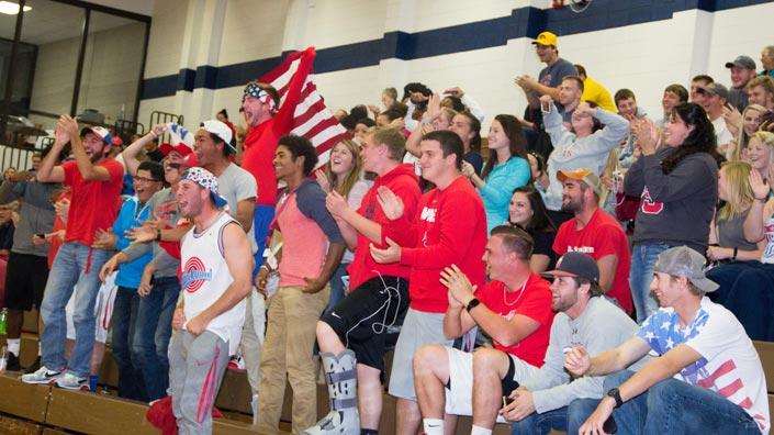 Students cheering in the stands at a home game.